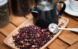 loose leaf rose petal tea on a wooden board with black tea pot
